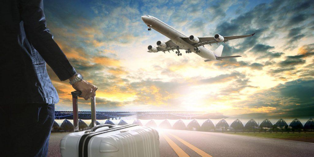 Osoba z walizką na tle odlatującego samolotu pasażerskiego