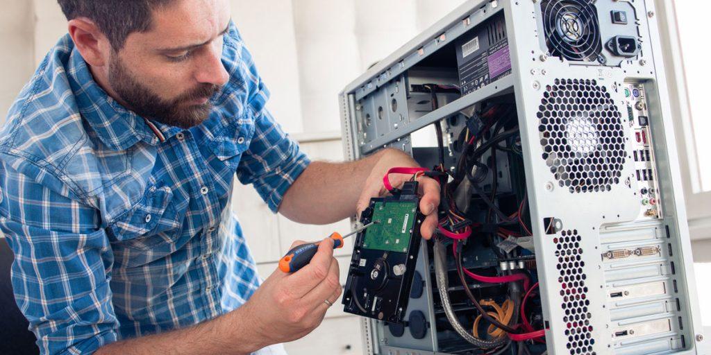 Informatyk przy rozkręconym komputerze naprawia twardy dysk