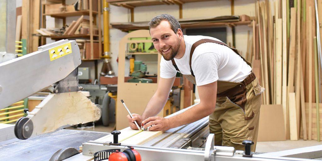 Stolarz przy pracy w zakładzie stolarskim